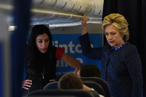 US Democratic presidential nominee Hillary Clinton talks to staff as aide Huma Abedin (L) listens onboard their campaign plane at the Westchester County Airport in White Plains, New York, on October 28, 2016. (JEWEL SAMAD/AFP/Getty Images)