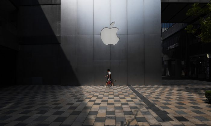 "A woman walks past an Apple store in Beijing on August 3, 2017.  Apple has removed software allowing internet users to skirt China's ""Great Firewall"" from its app store in the country, the company confirmed, sparking criticism that it was bowing to Beijing's web censorship. (Greg Baker/AFP/Getty Images)"
