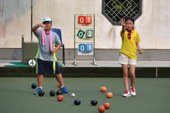 Jason Wong (right) and Summer Shen indicating to their skipper of the situation during the final of the 8-11 years old group at the U25 Age Group Lawn Bowls Competition. Shen, the defending champion, won three shots in this end but eventually lost 10:5. (Stephanie Worth)