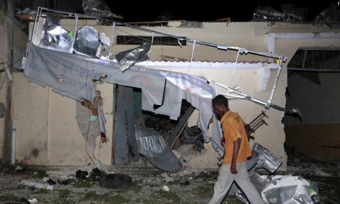 A local security guard walks past the scene after an explosion outside Darishifa hospital in Mogadishu, Somalia on Aug. 4, 2017. (REUTERS/Feisal Omar)