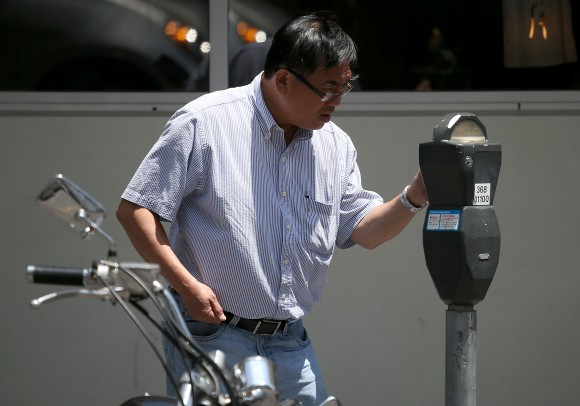 A motorist puts money into a parking meter on July 3, 2013 in San Francisco, California. (Justin Sullivan/Getty Images)