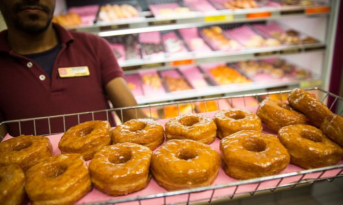 """A Dunkin' Donuts employee displays a fresh tray of """"croissant doughnuts.""""  (Photo by Andrew Burton/Getty Images)"""