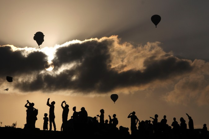 People watch and take photos of hot air balloons flying during the Gilboa Hot Air Balloon Festival near Kibbutz Ein Harod, Israel, on Aug. 4, 2017. (MENAHEM KAHANA/AFP/Getty Images)