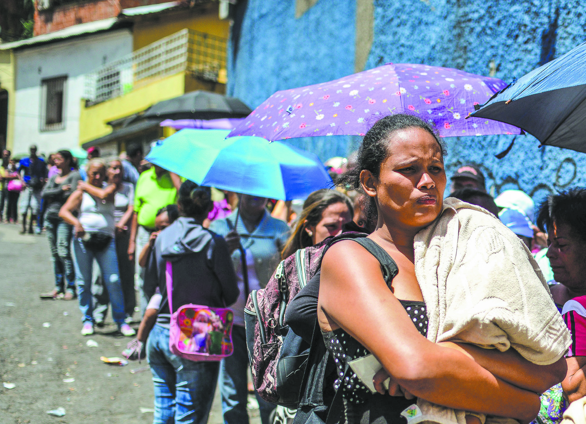 People line up to buy basic food and household items outside a supermarket in Caracas, Venezuela, in 2016. (RONALDO SCHEMIDT/AFP/GETTY IMAGES)