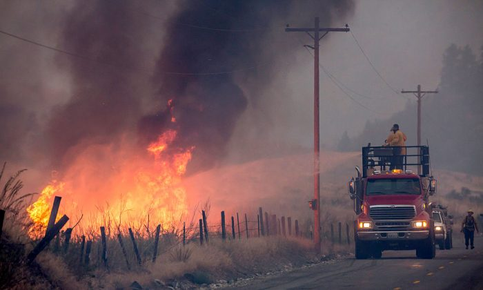 A makeshift fire truck puts water on a wildfire, which is part of the Okanogan Complex, as it burns through brush on August 22, 2015 near Omak, Washington. (Stephen Brashear/Getty Images)