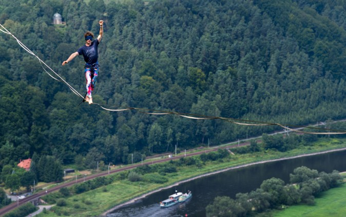 Slackliner Kai is blindfolded as he walks on a highline during an outdoor and trend sports festival over the Elbe river at the Koenigstein Fortress in Koenigstein, eastern Germany, on Aug. 5, 2017. (ARNO BURGI/AFP/Getty Images)