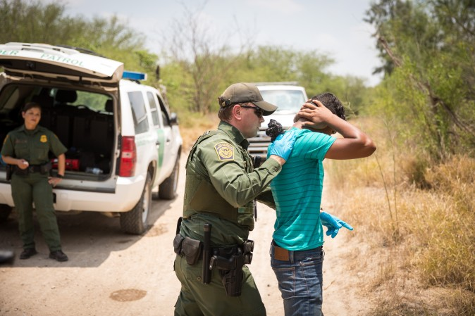 A Border Patrol Agent pats down a man who crossed the Rio Grande River from Mexico into the United States in Hidalgo County, Texas, on May 26, 2017. (Benjamin Chasteen/The Epoch Times)