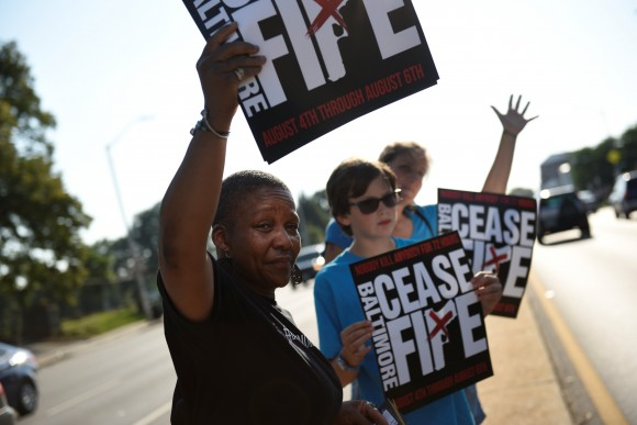 """People hold signs at the """"Stop the Violence"""" rally at the intersection of Edmondson Avenue and Wildwood Parkway during the 72 hour community-led Baltimore Ceasefire against gun violence in Baltimore, Maryland, U.S. August 4, 2017. (Reuters/Sait Serkan Gurbuz)"""