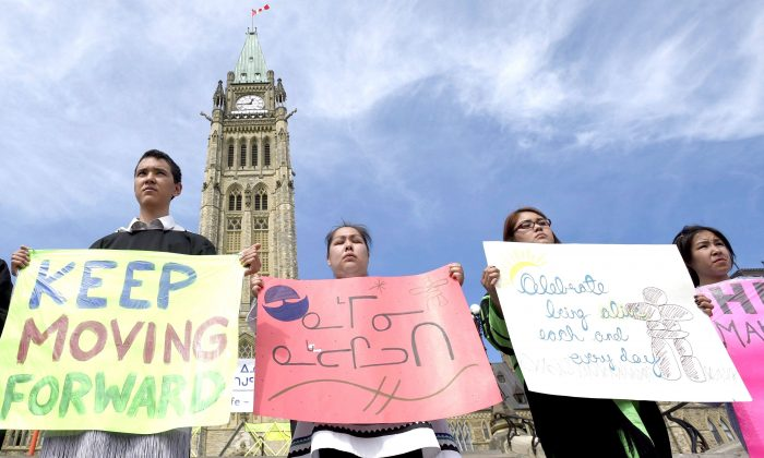 Students from the Nunavut Sivuniksavut program hold signs with hopeful messages in Inuktituk and English during a celebration of life on Parliament Hill on World Suicide Prevention Day, Sept. 10, 2015. (The Canadian Press/Justin Tang)