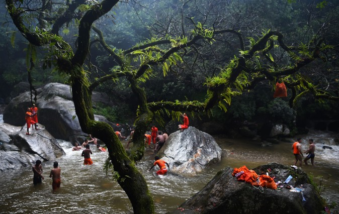 Hindu devotees bath and collect water in the Bagmati river on the outskirts of Kathmandu, Nepal, on Aug. 7, 2017. (PRAKASH MATHEMA/AFP/Getty Images)