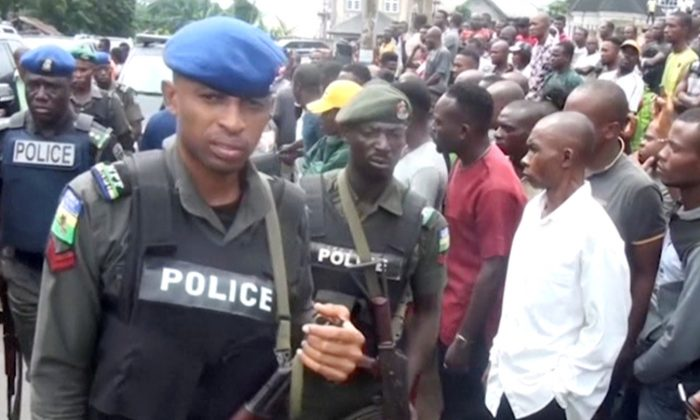 A still image taken from a video uploaded by CHANNELS TV on August 6, 2017, shows policemen clearing the way for security vehicle to drive in, outside St. Philips Catholic Church in Anambra, Nigeria. (CHANNELS TV via Reuters TV)