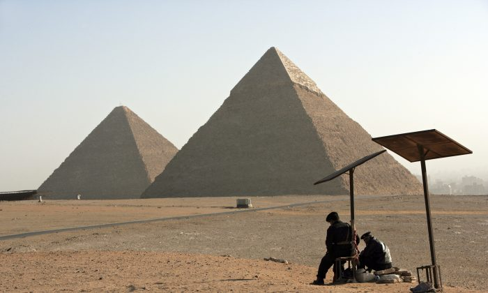 Two Egyptian Tourist Police Officers guard the area of the Great Pyramids Chephren and Mycerinus seen on the background in Giza, Cairo, Egypt. (Photo by Marco Di Lauro/Getty Images)