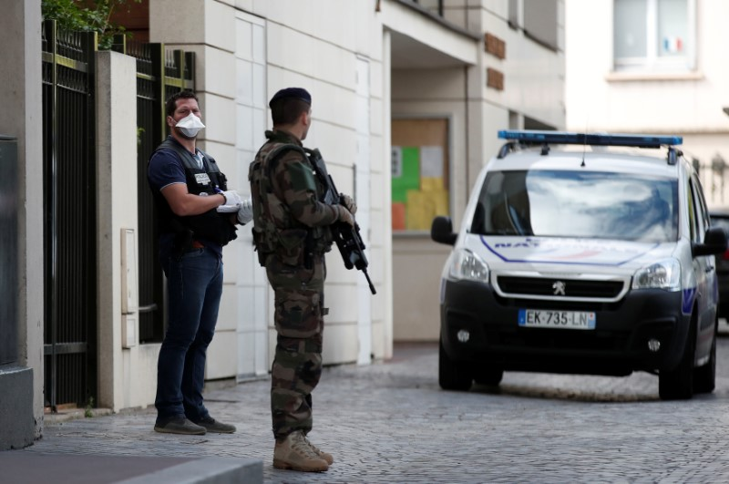 A police investigator and an armed soldier work near the scene where French soliders were hit and injured by a vehicle in the western Paris suburb of Levallois-Perret, France, August 9, 2017.     REUTERS/Benoit Tessier