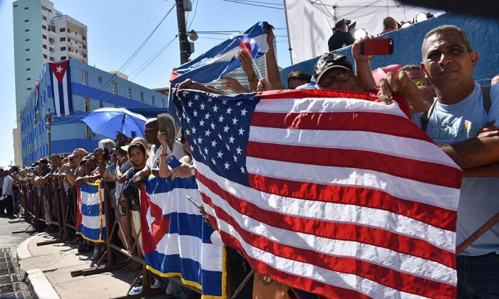 Cubans hold US and Cuban flags outside the US Embassy building as the US flag is raised over it in Havana. (ADALBERTO ROQUE/AFP/Getty Images)