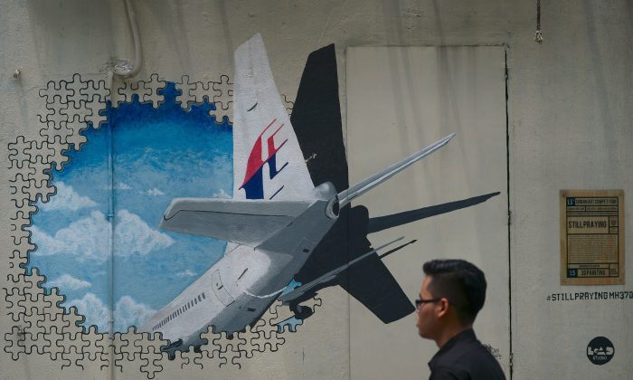 A man walks pasts a mural representing the missing Malaysia Airlines flight MH370 at an alley in Shah Alam, on the outskirts of Kuala Lumpur on Aug. 26, 2015. (MOHD RASFAN/AFP/Getty Images)