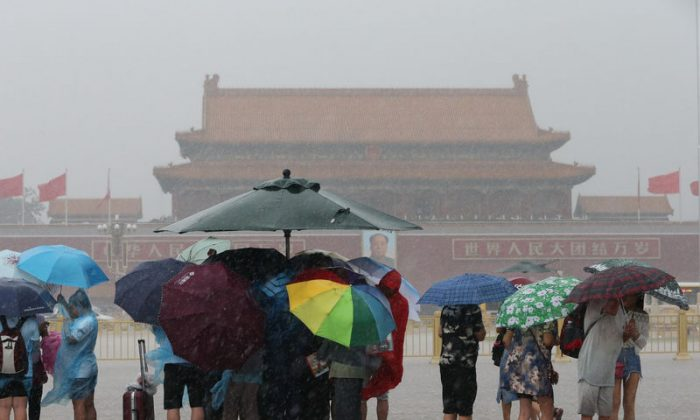 Tourists hold umbrellas as they visit Tiananmen Square during a rainstorm in Beijing, China August 12, 2017. (Reuters/Stringer)