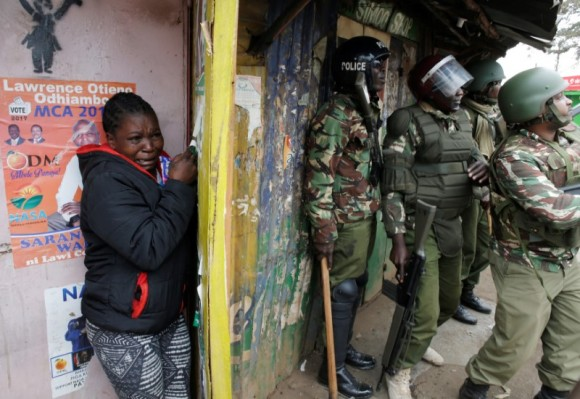 A woman cries as she stand behind policemen during clashes between supporter of opposition leader Raila Odinga and policemen in Kibera slum in Nairobi, Kenya, August 12, 2017.   (Reuters/Goran Tomasevic)