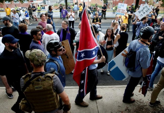 A white supremacists carries the Confederate flag as he walks past counter demonstrators in Charlottesville, Virginia, U.S., August 12, 2017.   REUTERS/Joshua Roberts