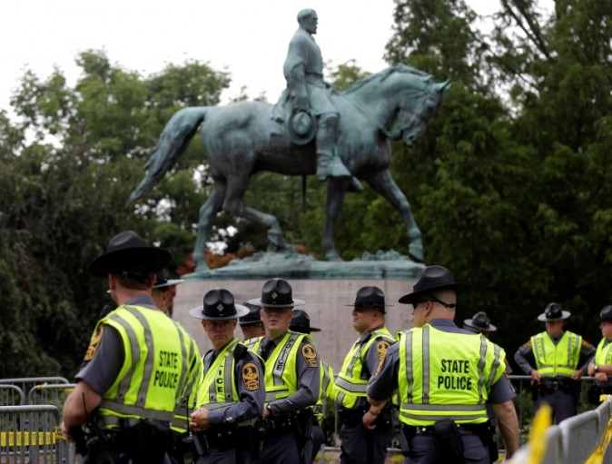Virginia State Troopers stand under a statue of Robert E. Lee before a white supremacists rally in Charlottesville, Virginia, U.S., August 12, 2017.   REUTERS/Joshua Roberts
