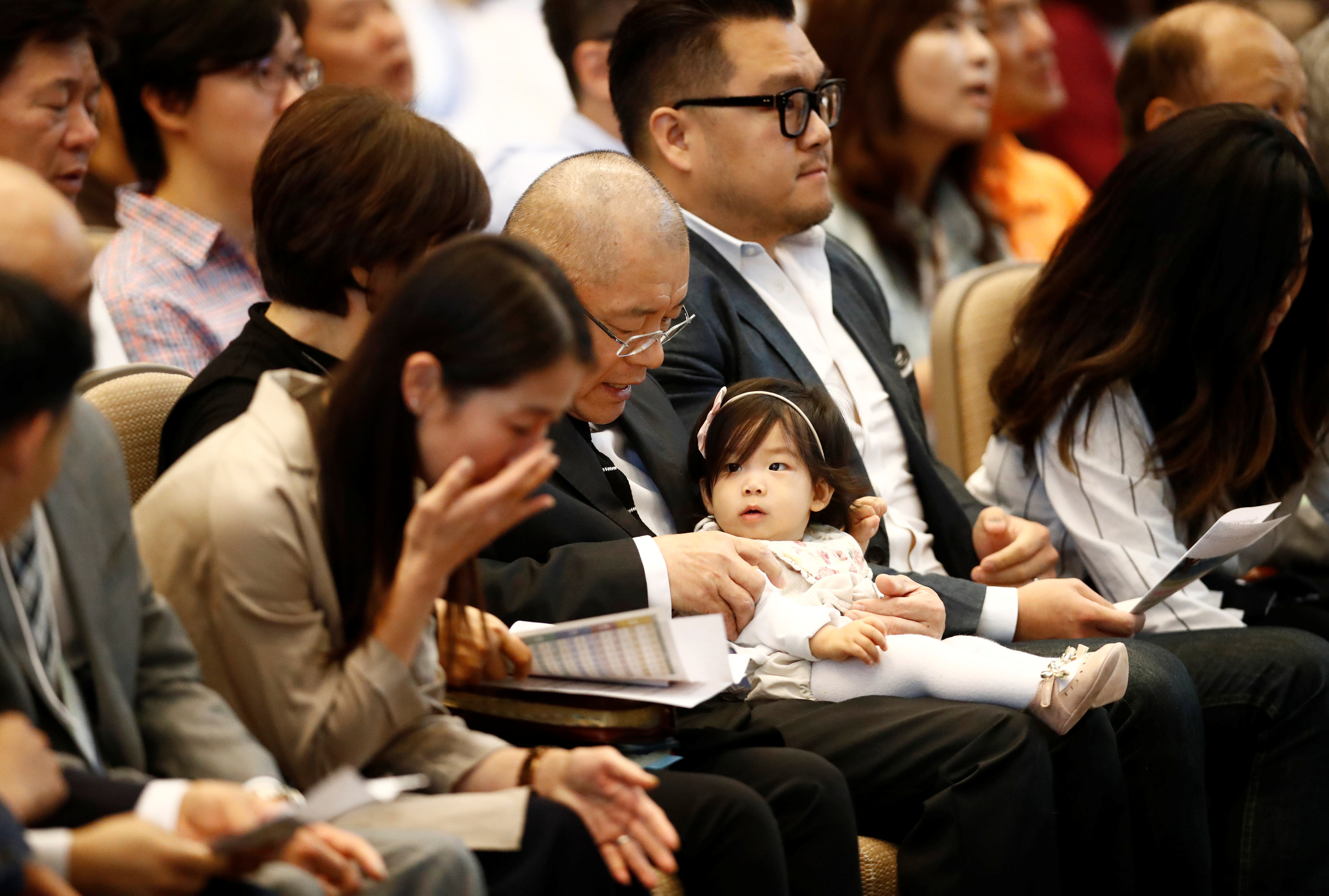 Pastor Hyeon Soo Lim, who returned to Canada from North Korea after the DPRK released Lim on August 9, after being held for 31 months, holds his granddaughter beside his son James, at the Light Presbyterian Church in Mississauga, Ontario, Canada on August 13, 2017.    (REUTERS/Mark Blinch)