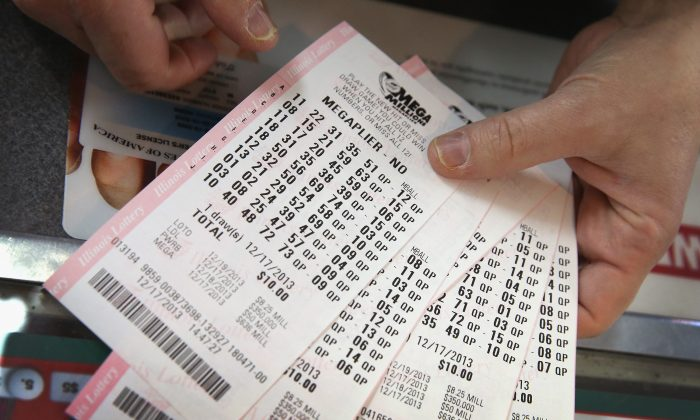 A customer holds a stack of Mega Millions lottery tickets which he purchased for his office pool at a convenience store in Chicago, Illinois on Dec. 17, 2013. (Scott Olson/Getty Images)