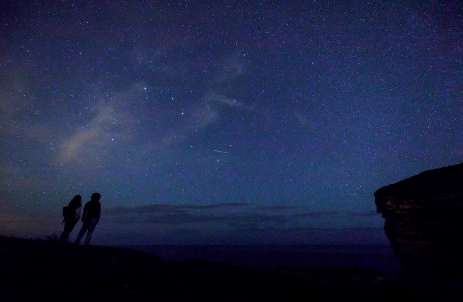 """A couple watches the Perseid meteor shower along the Milky Way illuminating the dark sky near Comillas, Cantabria community, northern Spain, on Aug. 13. Northern hemisphere sky-gazers are in for a special treat on August 11 and 13, night with a rare shooting star """"outburst"""", which astronomers hope will not be marred by clouds and a bright Moon. (CESAR MANSO/AFP/Getty Images)"""