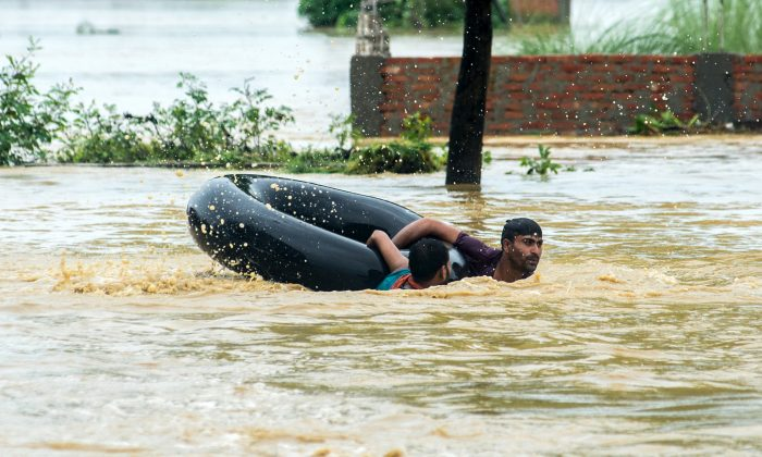 Nepali residents swim with a rubber ring in a flooded area in the Birgunj Parsa district, some 200km south of Kathmandu, on August 13, 2017. (MANISH PAUDEL/AFP/Getty Images)