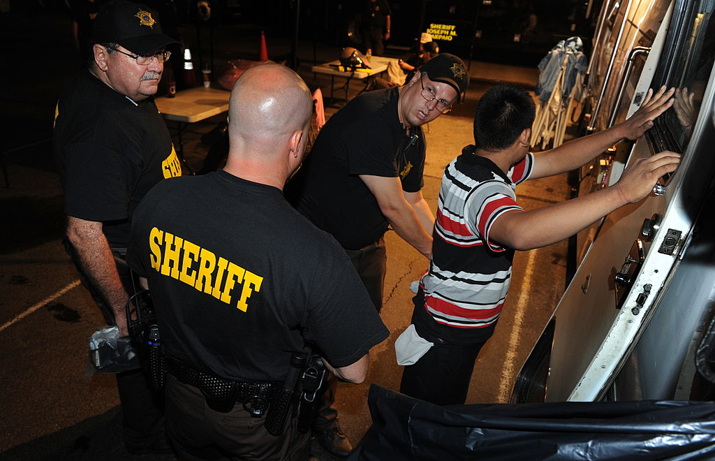 An illegal immigrant is processed by Sheriff's Deputies working for Maricopa County sheriff Joe Arpaio, after an operational sweep in Phoenix on July 29, 2010. MARK RALSTON/AFP/Getty Images)