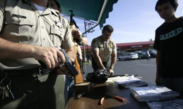 Los Angeles Sheriff officers secure a handgun during a gifts-for-guns exchange program in Compton, CA.(HECTOR MATA/AFP/Getty Images)