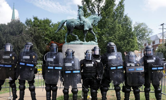 """Virginia State Police in riot gear stand in front of the statue of General Robert E. Lee before forcing white nationalists, neo-Nazis and members of the """"alt-right"""" out of Emancipation Park after the """"Unite the Right"""" rally was declared an unlawful gathering Aug. 12, 2017 in Charlottesville, Virginia. (Chip Somodevilla/Getty Images)"""
