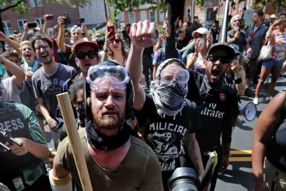 """Armed members of the Antifa extremist group wait outside Emancipation Park to hurl insults as members of various groups, including white nationalists and neo-Nazis, are forced out after the """"Unite the Right"""" rally was declared an unlawful gathering August 12, 2017 in Charlottesville, Virginia.   Police officers stood down as the Antifa extremist group assaulted the people exiting the park. (Chip Somodevilla/Getty Images)"""