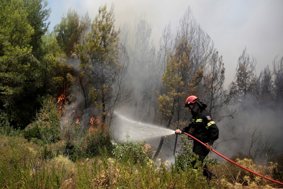 A firefighter tries to extinguish a wildfire burning near the village of Kalamos, north of Athens, Greece, August 14, 2017. (Reuters/Costas Baltas)