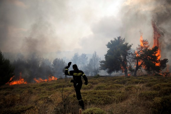 A firefighter walks on a field as flames rise during a wildfire near the village of Kapandriti, north of Athens, Greece, August 15, 2017. (Reuters/Alkis Konstantinidis)