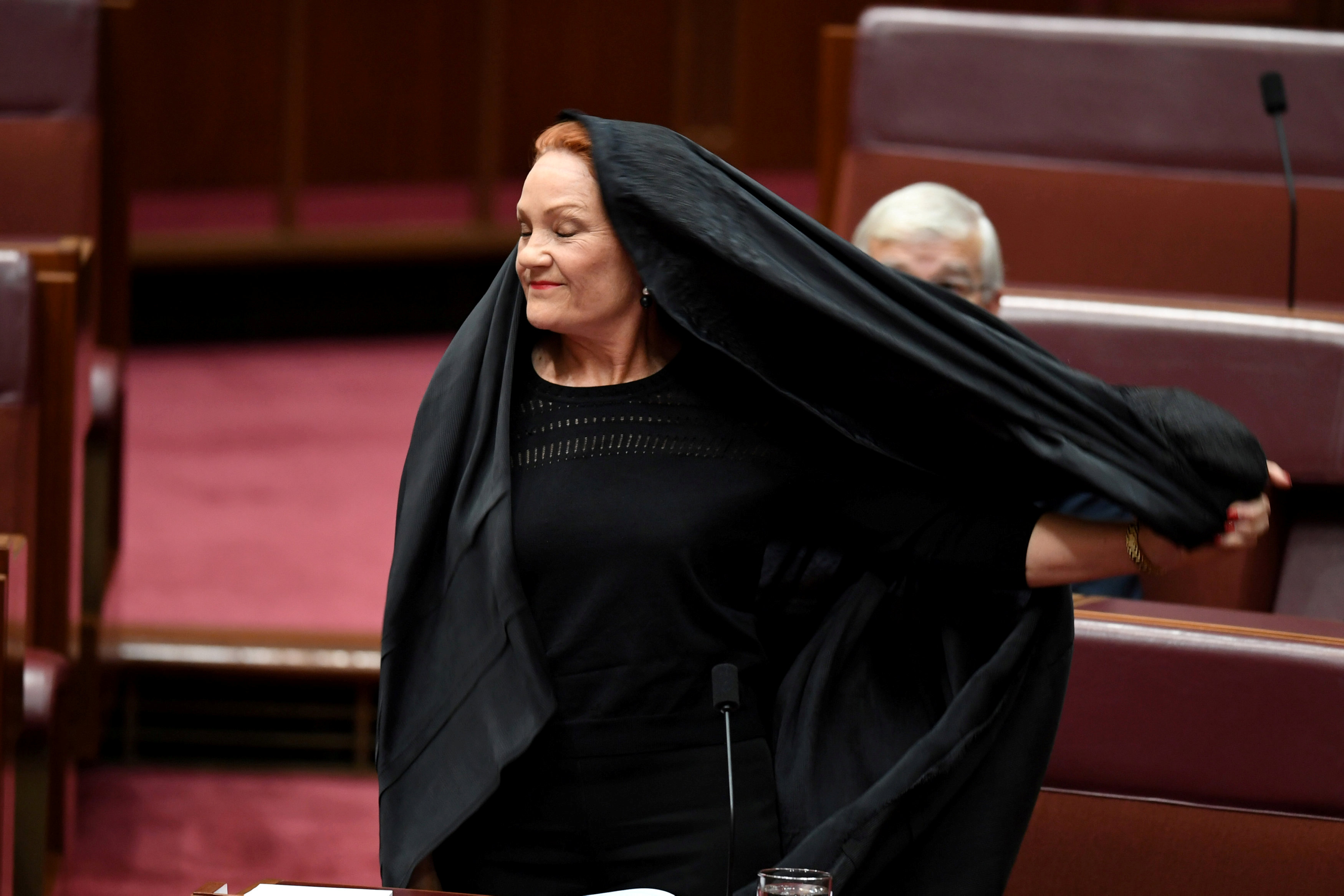 Australian One Nation party leader, Senator Pauline Hanson pulls off a burqa in the Senate chamber at Parliament House in Canberra, Australia, August 17, 2017.  AAP/Mick Tsikas/via REUTERS