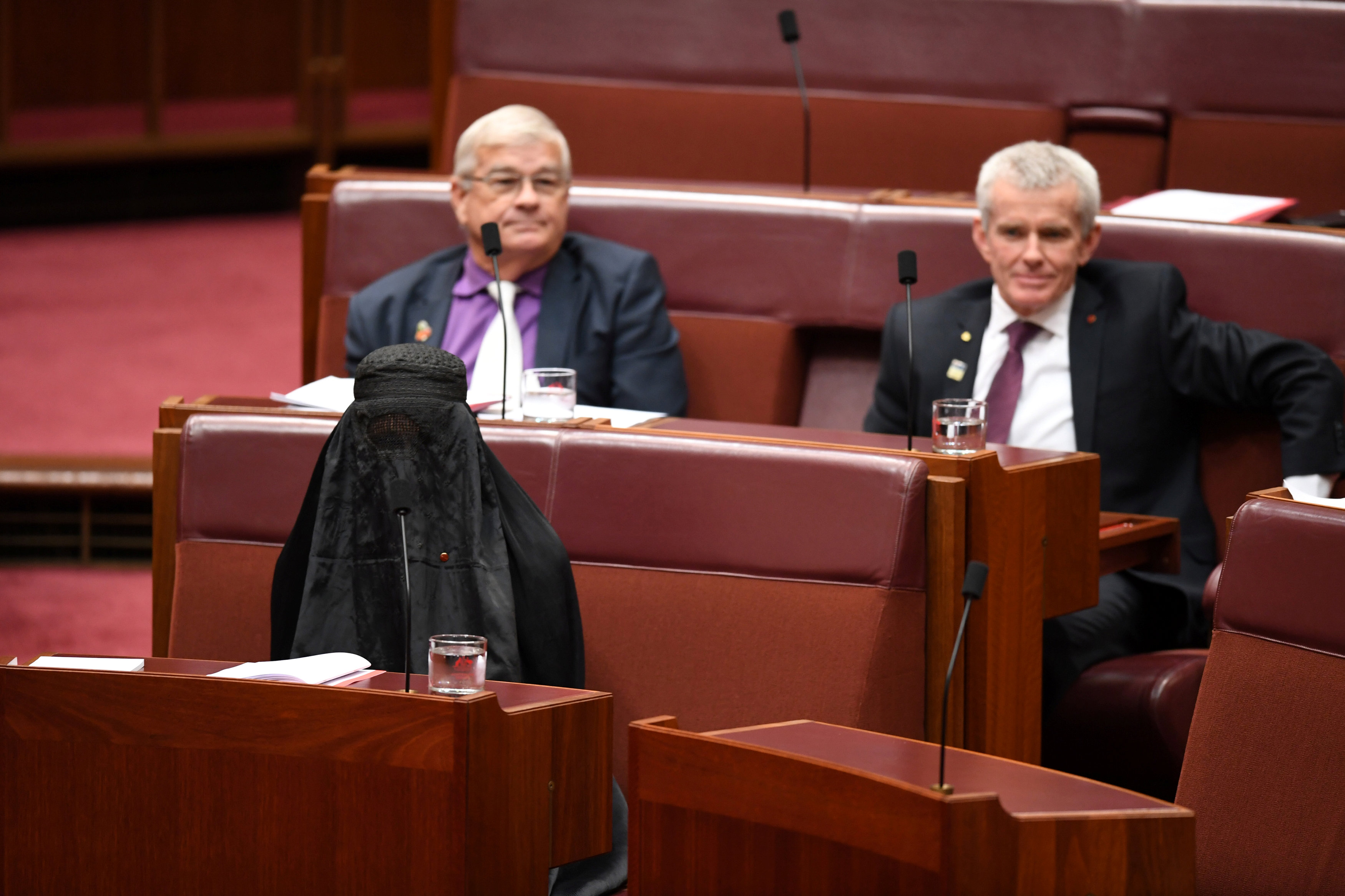 Australian One Nation party leader, Senator Pauline Hanson (L) wears a burqa in the Senate chamber at Parliament House in Canberra, Australia, August 17, 2017.  (AAP/Mick Tsikas/via REUTERS)