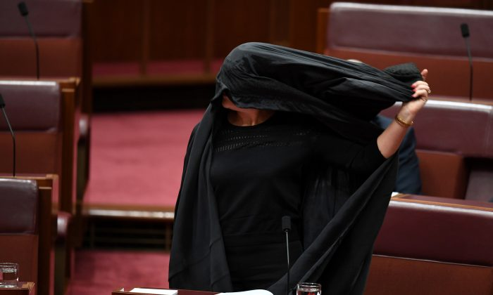 Australian One Nation party leader, Senator Pauline Hanson pulls off a burqa in the Senate chamber at Parliament House in Canberra, Australia, August 17, 2017.  (AAP/Mick Tsikas/via REUTERS)