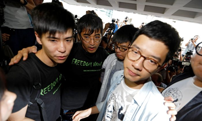 Student leaders Lester Shum, Alex Chow, Joshua Wong and Nathan Law hold hands as they walk into the High Court to face verdict on charges relating to the 2014 pro-democracy Umbrella Movement, also known as Occupy Central protests, in Hong Kong, China on August 17, 2017. (REUTERS/Tyrone Siu)