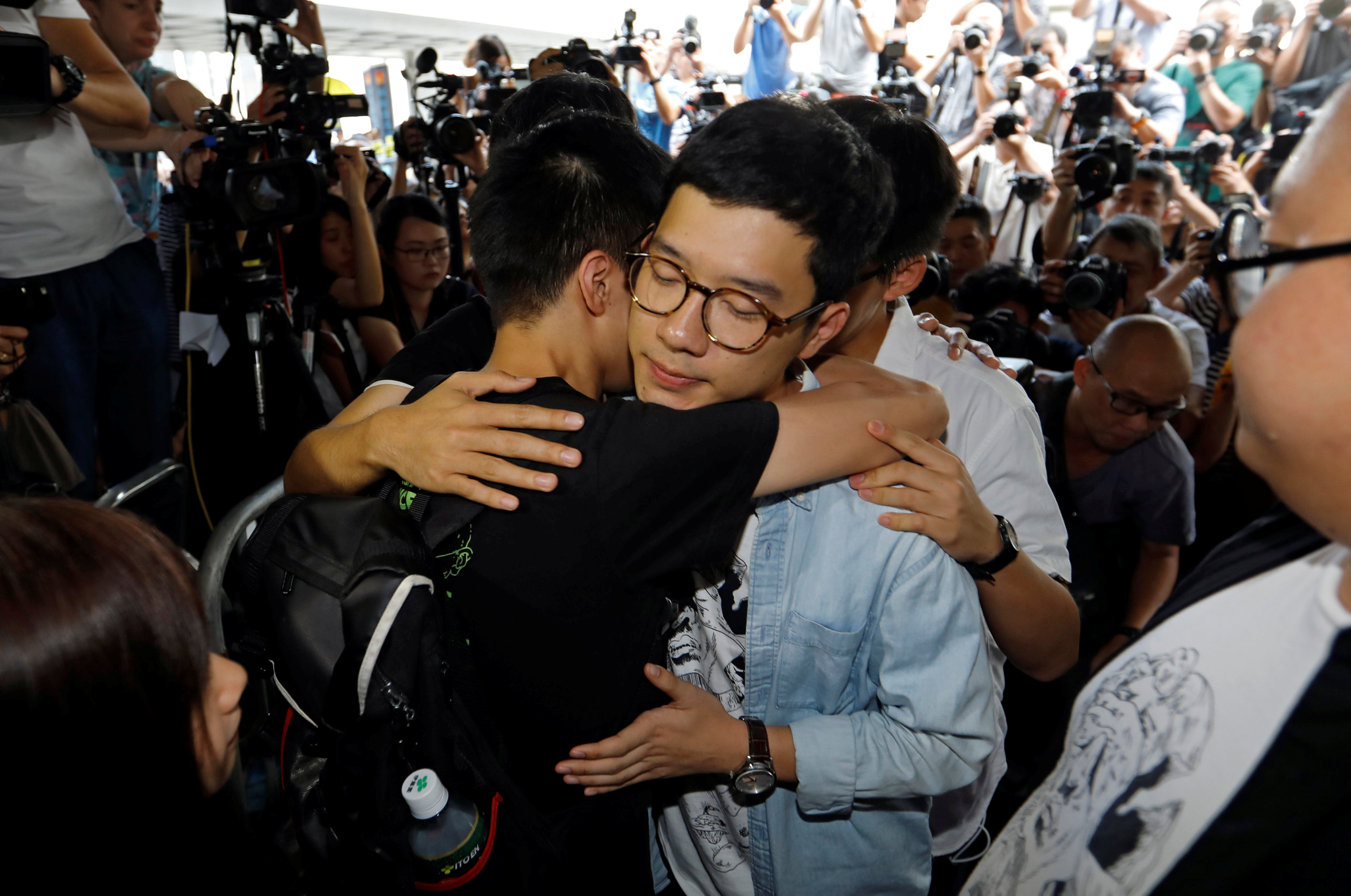 Student leaders Nathan Law and Joshua Wong hug Lester Shum as they arrive at the High Court to face verdict on charges relating to the 2014 pro-democracy Umbrella Movement, also known as Occupy Central protests, in Hong Kong, China on August 17, 2017. (REUTERS/Tyrone Siu)