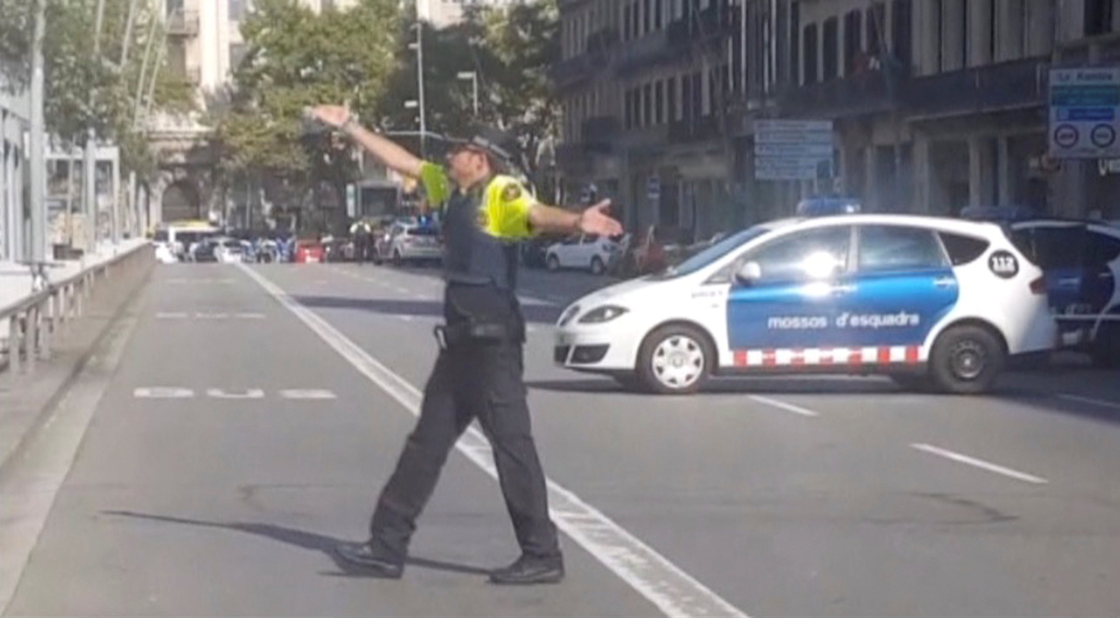 A still image from video shows a police officer gesturing while walking across a road, after a van crashed into people in the centre of Barcelona, Spain on Aug. 17, 2017. (REUTERS TV via REUTERS)