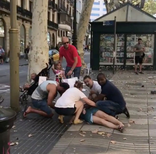 People help an injured woman lying on the ground after a van crashed into pedestrians near the Las Ramblas avenue in central Barcelona, Spain August 17, 2017, in this still image from a video obtained from social media. Courtesy of Carlos Tena Gallardo/via REUTERS