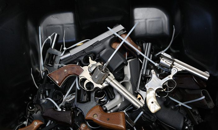Surrendered handguns are piled in a bin. (Photo by David McNew/Getty Images)