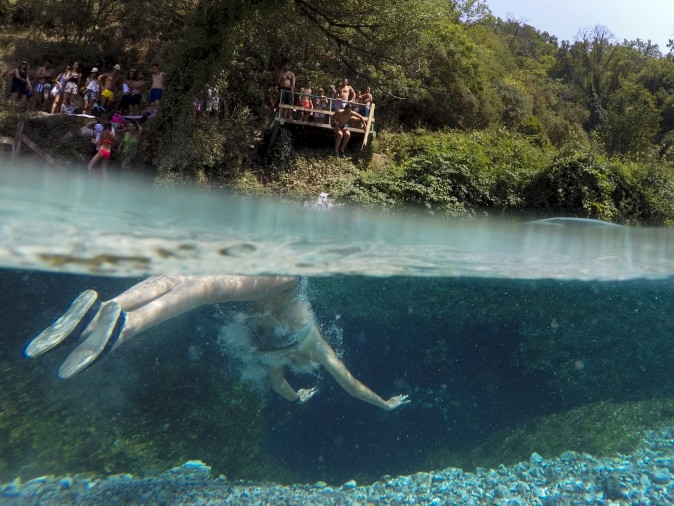 A man swims in the Blue Eye water spring near the city of Sarande, Albania, on Aug. 16, 2017. The clear water of the Blue Eye spring flows from a 50 meters deep pool with a temperature of 10 degrees Celsius (50 °F). (GENT SHKULLAKU/AFP/Getty Images)