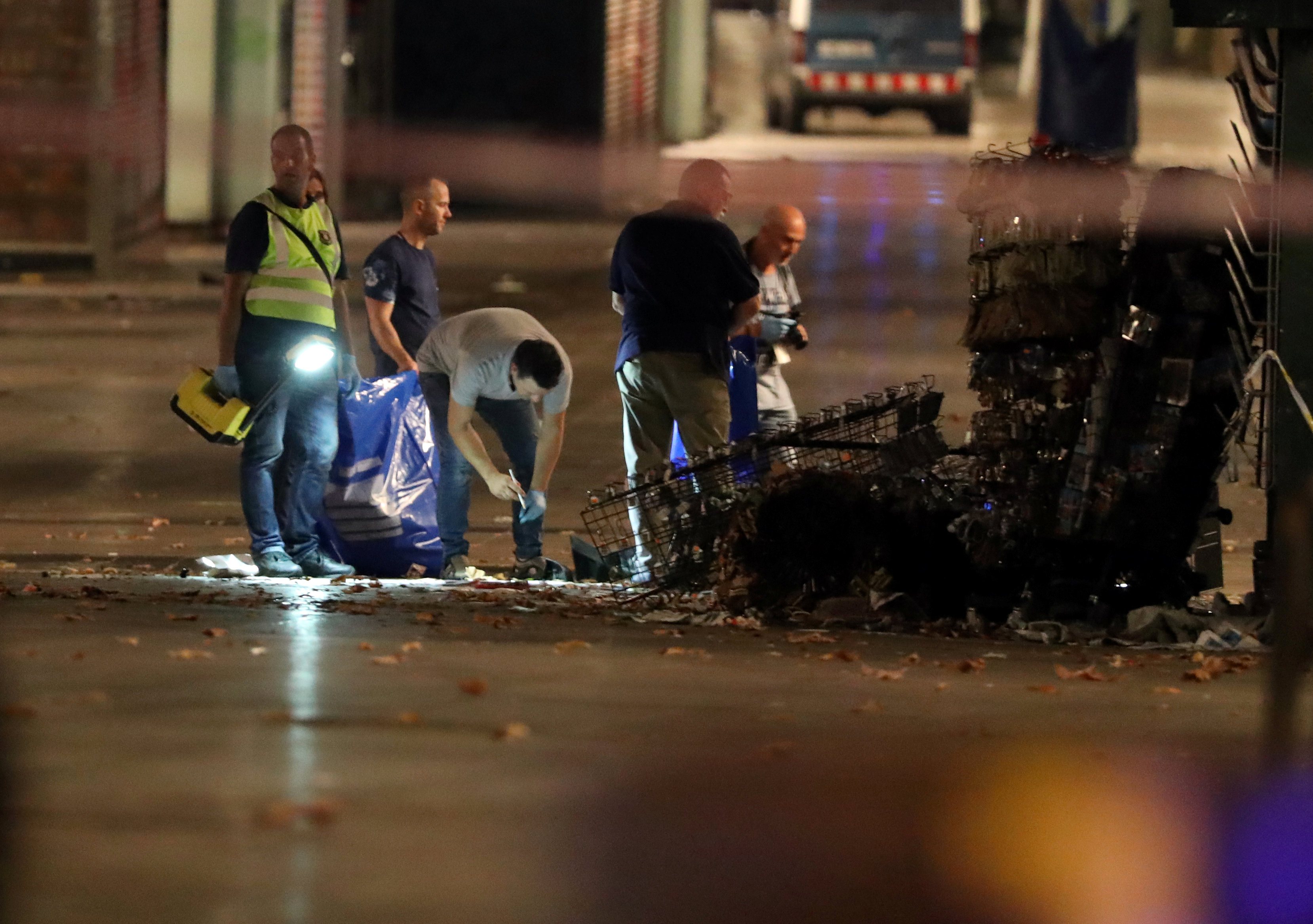 Forensic police officers search for clues near the area where a van crashed into pedestrians at Las Ramblas in Barcelona, Spain, August 18, 2017. (REUTERS/Sergio Perez)