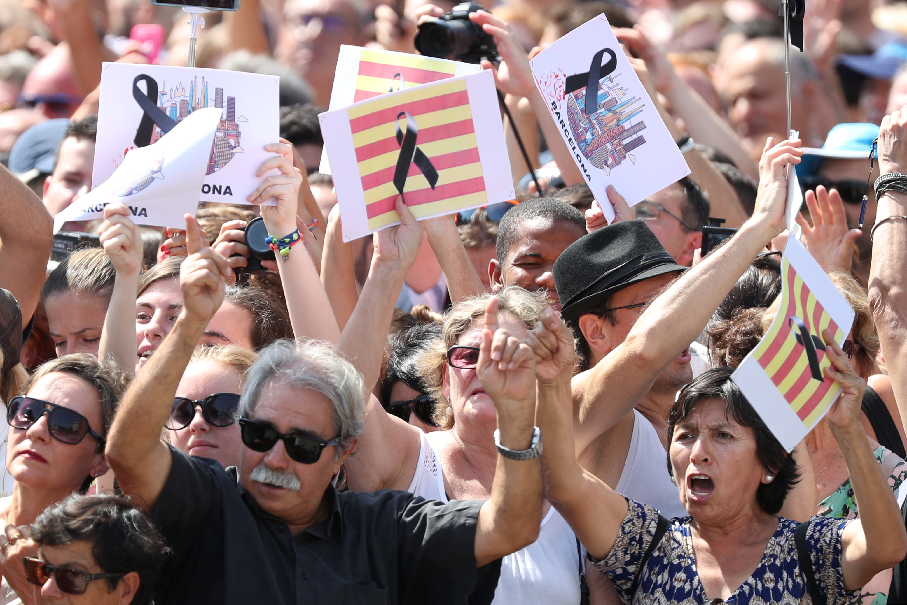 People hold banners as they observe a minute of silence in Placa de Catalunya, a day after a van crashed into pedestrians at Las Ramblas in Barcelona, Spain August 18, 2017. (REUTERS/Sergio Perez)