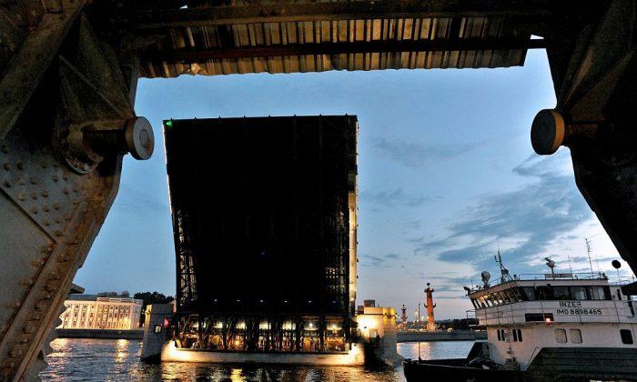 A cargo ship sails along the river under a drawbridge. (OLGA MALTSEVA/AFP/Getty Images)