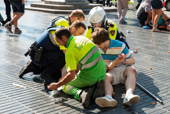 A person is helped by Spanish policemen and two men after a van ploughed into the crowd, killing at least 13 people and injuring around 100 others on the Rambla in Barcelona on August 17, 2017. (NICOLAS CARVALHO OCHOA/AFP/Getty Images)