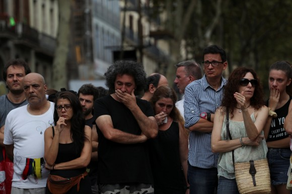 People react at an impromptu memorial where a van crashed into pedestrians at Las Ramblas in Barcelona, Spain, August 19, 2017. (Reuters/Sergio Perez)
