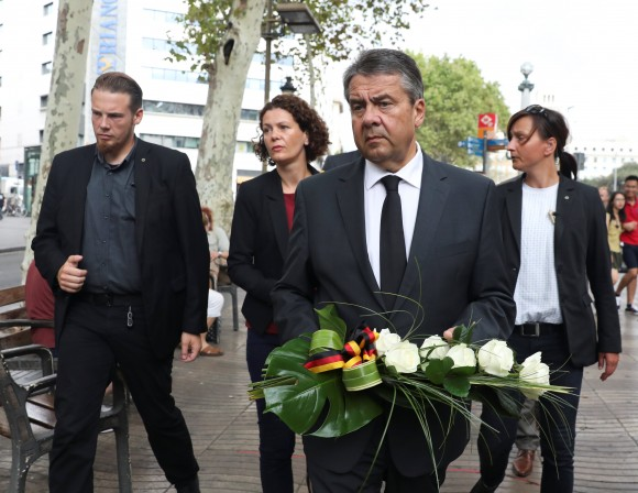 German Foreign Minister Gabriel holds flowers before placing it at an impromptu memorial where a van crashed into pedestrians at Las Ramblas in Barcelona, Spain, August 19, 2017. (Reuters/Sergio Perez)