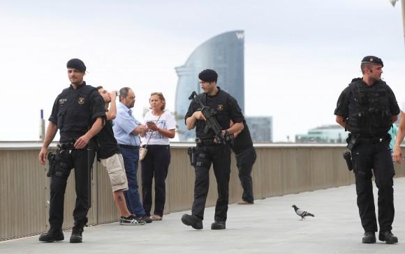 Armed Catalan Mossos d'Esquadra officers patrol along La Barceloneta beach in Barcelona, Spain, August 19, 2017. (Reuters/Sergio Perez)