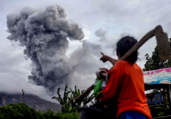 An Indonesian villager gestures as Mount Sinabung volcano spews thick volcanic ash, in Karo, North Sumatra on July 8, 2017. (AFP/Getty Images)